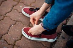 Δένοντας κορδόνι γυναικών στο πάρκο Περιστασιακά ορισμένα πάνινα παπούτσια Στοκ Εικόνες