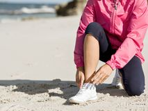 Δένοντας κορδόνι δρομέων γυναικών στην παραλία Στοκ εικόνα με δικαίωμα ελεύθερης χρήσης
