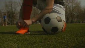 Δένοντας κορδόνι ποδοσφαιριστών στην πίσσα ποδοσφαίρου απόθεμα βίντεο