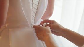 Δένοντας τόξο παράνυμφων στο γαμήλιο φόρεμα Νύφη που παίρνει έτοιμη για τη γαμήλια τελετή Κινηματογράφηση σε πρώτο πλάνο γαμήλιων απόθεμα βίντεο