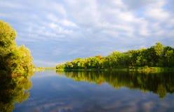 Δέντρα και σύννεφα που απεικονίζονται στον ποταμό Στοκ εικόνα με δικαίωμα ελεύθερης χρήσης