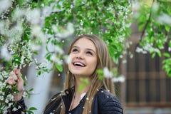 Δέντρο κοριτσιών ανθίζοντας πλησίον κορίτσι με το μακρυμάλλες και όμορφο πρόσωπο Στοκ Φωτογραφία