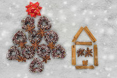 Δέντρο μπισκότων Χριστουγέννων κοντά σε ένα σπίτι που γίνεται από την κανέλα με το χιονώδες υπόβαθρο Στοκ Εικόνα