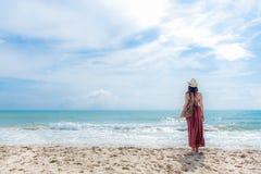 δέντρο πεδίων Η χαμογελώντας γυναίκα που φορά το καλοκαίρι μόδας που στέκεται και βλέπει την αμμώδη ωκεάνια παραλία Η ευτυχής γυν Στοκ Εικόνα