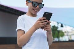 δέντρο πεδίων Χαμογελώντας αγόρι στις άσπρες στάσεις μπλουζών και γυαλιών ηλίου υπαίθριες και το smartphone χρήσεων Το αγόρι παίζ Στοκ Εικόνα
