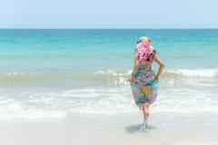 δέντρο πεδίων Χαμογελώντας γυναίκα που φορά το καλοκαίρι μόδας που περπατά στην αμμώδη ωκεάνια παραλία Στοκ εικόνα με δικαίωμα ελεύθερης χρήσης