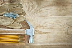 Δέρματος προστατευτικά καρφιά σφυριών νυχιών μετρητών γαντιών ξύλινα στο ξύλο Στοκ εικόνα με δικαίωμα ελεύθερης χρήσης