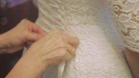 Δέσιμο του γαμήλιου φορέματος closeup φιλμ μικρού μήκους