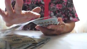 Δέσμη εκμετάλλευσης γιαγιάδων των χρημάτων στα χέρια και τη ρίψη των λογαριασμών εκατό δολαρίων στον πίνακα Όπλα της ηλικιωμένης  απόθεμα βίντεο