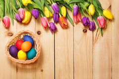 Δέσμη λουλουδιών άνοιξη και αυγά Πάσχας στην ξύλινη σύσταση πατωμάτων beaujolais Στοκ εικόνες με δικαίωμα ελεύθερης χρήσης