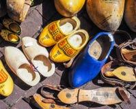 Δέσμη παλαιά ολλανδικά παραδοσιακά ξύλινα clogs, μερικά που χρωματίζονται, μερικά στοκ φωτογραφίες