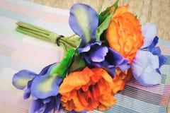 Δέσμη του πορτοκαλιού τεχνητού βατραχίου με τα μπλε λουλούδια Στοκ Εικόνες