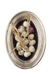Δέσμη του σκόρδου σε μια ασημένια ωοειδή πιατέλα - που απομονώνεται στο λευκό Στοκ εικόνες με δικαίωμα ελεύθερης χρήσης