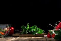 Δέσμη του φρέσκου σπανακιού με τα διάφορα λαχανικά στον ξύλινο πίνακα Στοκ Φωτογραφία