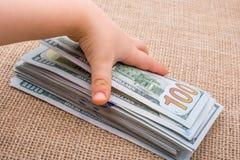 Δέσμη τραπεζογραμματίων εκμετάλλευσης χεριών μικρών παιδιών του αμερικανικού δολαρίου υπό εξέταση Στοκ φωτογραφία με δικαίωμα ελεύθερης χρήσης