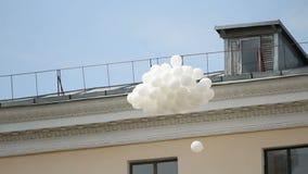 Δέσμη των άσπρων μπαλονιών που πετούν στο μπλε ουρανό, παραδοσιακή τελετή, περιβάλλον φιλμ μικρού μήκους