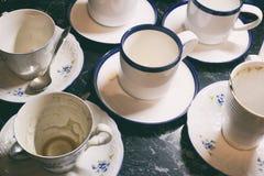 Δέσμη των βρώμικων χρησιμοποιημένων άσπρων φλυτζανιών μετά από να πιει τον καφέ ή το τσάι μετά από το κόμμα Στοκ Εικόνες