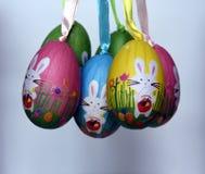 Δέσμη των ζωηρόχρωμων ασθμαμένων πλαστικών αυγών με τα άσπρα λαγουδάκια Στοκ Εικόνες