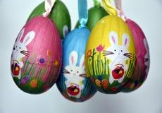 Δέσμη των ζωηρόχρωμων ασθμαμένων πλαστικών αυγών με τα άσπρα λαγουδάκια Στοκ Εικόνα