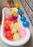 Δέσμη των ζωηρόχρωμων μπαλονιών στο σωλήνα λουτρών Μεγάλος σωρός των πολύχρωμων διογκωμένων μπαλονιών Στοκ Φωτογραφίες