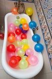Δέσμη των ζωηρόχρωμων μπαλονιών στο σωλήνα λουτρών Μεγάλος σωρός των πολύχρωμων διογκωμένων μπαλονιών Στοκ Εικόνα