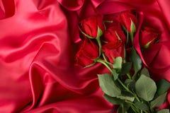 Δέσμη των τριαντάφυλλων στο κλωστοϋφαντουργικό προϊόν Στοκ Εικόνες