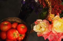 Δέσμη των τριαντάφυλλων γύρω από το καλάθι με τα μήλα στο υπόβαθρο Στοκ Φωτογραφίες