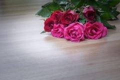 Δέσμη των τριαντάφυλλων στην ξύλινη επιφάνεια με το διάστημα για το κείμενο Στοκ Φωτογραφία