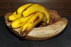 δέσμη των ώριμων κίτρινων μπανανών σε ένα ξύλινο κύπελλο στοκ εικόνες με δικαίωμα ελεύθερης χρήσης