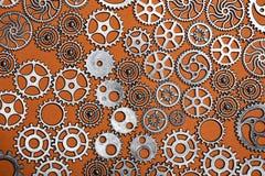 Δέσμη cogwheels σε ένα πορτοκαλί υπόβαθρο Στοκ Εικόνες