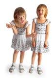 Δίδυμα αδελφών στο άσπρο παιχνίδι φορεμάτων Στοκ Φωτογραφία