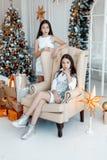 Δίδυμα κοριτσιών μπροστά από fir-tree Νέα παραμονή έτους ` s Χριστούγεννα Άνετες διακοπές fir-tree με τα φω'τα στοκ εικόνα με δικαίωμα ελεύθερης χρήσης