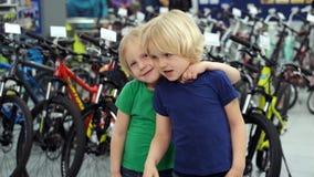 Δίδυμα που αγκαλιάζουν το ένα το άλλο σε ένα αθλητικό κατάστημα απόθεμα βίντεο