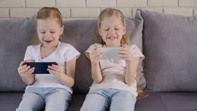 Δίδυμα που χρησιμοποιούν smatphones στον καναπέ απόθεμα βίντεο