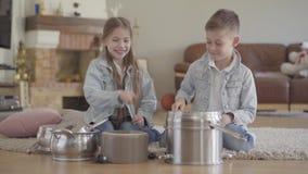 Δίδυμοι παίζοντας μουσικοί αδελφών και αδελφών που κτυπούν τα δοχεία και τα πιάτα με τα μεγάλα κουτάλια και γέλιο που έχει τη δια απόθεμα βίντεο