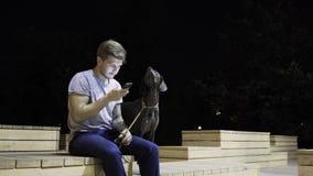 Δίκαιος Ιστός τύπων τρίχας που κάνει σερφ σε έναν πάγκο σε ένα πάρκο νύχτας με το σκυλί του φιλμ μικρού μήκους