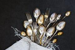 Δίκρανα, κουτάλια και κουταλάκια του γλυκού με το τραπεζομάντιλο Στοκ Φωτογραφίες