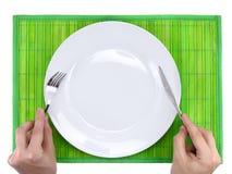 Δίκρανο και μαχαίρι λαβής χεριών επάνω από το πιάτο. Στοκ Φωτογραφίες