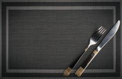 Δίκρανο και μαχαίρι με τα χρυσά στοιχεία σε ένα placemat στοκ εικόνες