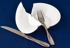 Δίκρανο και μαχαίρι που βρίσκονται στο σπασμένο άσπρο πιάτο Στοκ Φωτογραφία