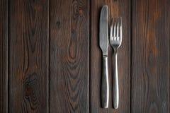 Δίκρανο και μαχαίρι στο σκοτεινό ξύλινο υπόβαθρο Στοκ Εικόνες