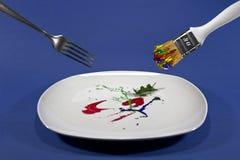 Δίκρανο και πινέλο επάνω από το πιάτο με το χρώμα Στοκ φωτογραφία με δικαίωμα ελεύθερης χρήσης