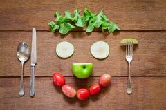 Δίκρανο, κουτάλι, μαχαίρι και χαμόγελο διαμορφωμένα λαχανικά σαλάτας στο ξύλινο υπόβαθρο grunge Στοκ Εικόνες