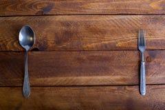 Δίκρανο, κουτάλι, μαχαίρι στο ξύλινο επιτραπέζιο υπόβαθρο με το αντίγραφο plac Στοκ Εικόνες