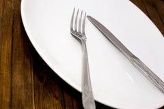 Δίκρανο με το μαχαίρι, άσπρο πιάτο Στοκ εικόνα με δικαίωμα ελεύθερης χρήσης