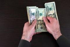 Δίνει τα μετρώντας τραπεζογραμμάτια δολαρίων στη σκοτεινή ξύλινη επιφάνεια στοκ φωτογραφίες