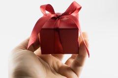 Δίνοντας ένα δώρο, όμορφο κόκκινο δώρο παρόν σε ένα άσπρο υπόβαθρο Στοκ Φωτογραφίες