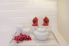 Δίσκος γυαλιού με άσπρο teapot, τα φλυτζάνια και τα κόκκινα σταφύλια στοκ εικόνα