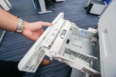 Δίσκος εκτυπωτών γραφείων τραβήγματος επιχειρηματιών για το φύλλο εγγράφου εισαγωγής Στοκ Εικόνες