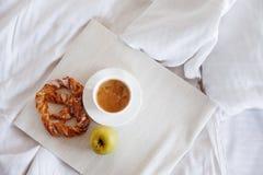 Δίσκος με το πρόγευμα σε ένα κρεβάτι Γλυκό pretzel, φλιτζάνι του καφέ και Apple Τοπ όψη Στοκ εικόνα με δικαίωμα ελεύθερης χρήσης
